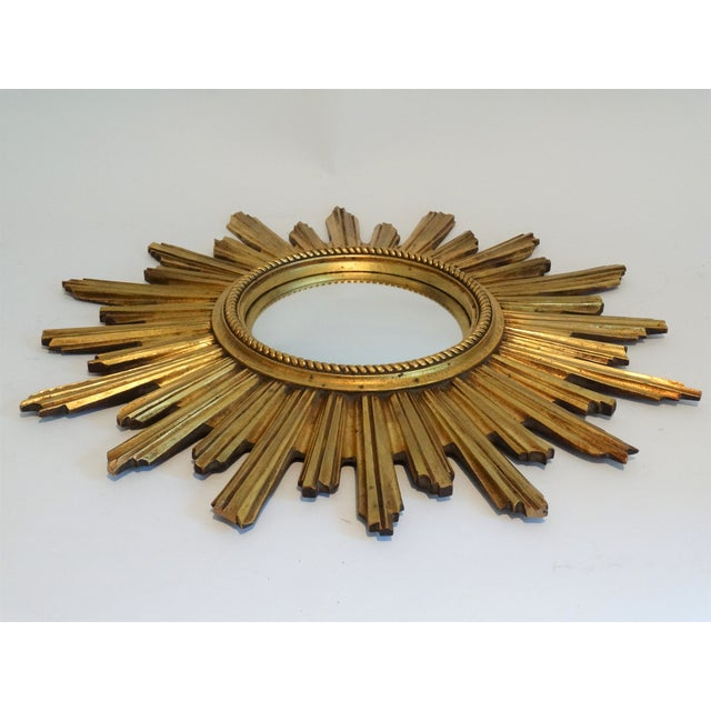 A large gilt wood convex sunburst mirror with lovely stepped dimensional rays. It was made in Belgium in northern Europe....