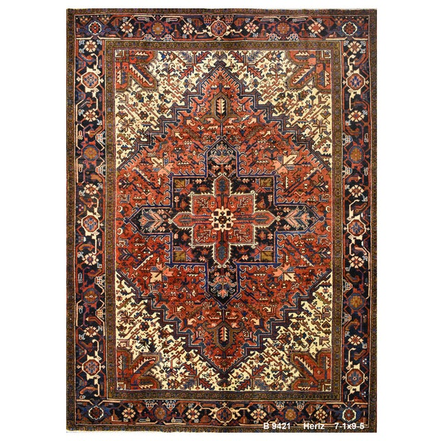 This beautiful rug is hand made, made in Iran. It features a pattern in a vibrant combination of red, navy,blue, white....