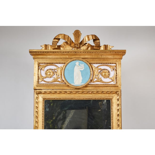 The console with a veined white marble top, the frieze carved with foliate design motifs and central medallion on tapered...