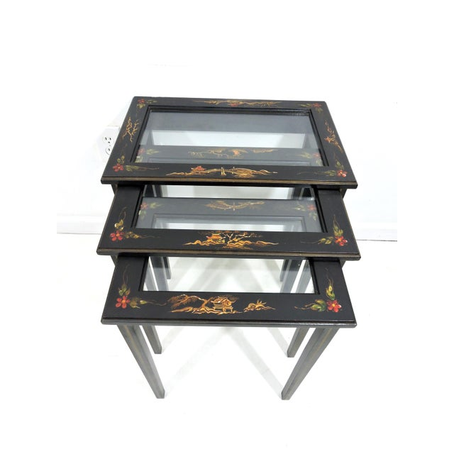 A set of three quite delightful hand painted side tables with inset glass tops. Each of the nesting tables has a small...