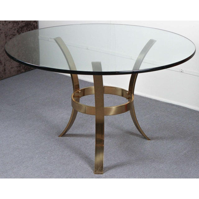 Large entry table with a beefy tripod base of polished brass and a circular glass top. The base is detailed with bolts...