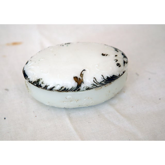 Offered is a darling oval milk glass trinket box with aged gold trim.
