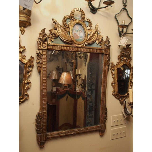 Carved gilt wood frame, Louis XVI style, small painting in oval cartouche at crest, flag, and carved leaves.