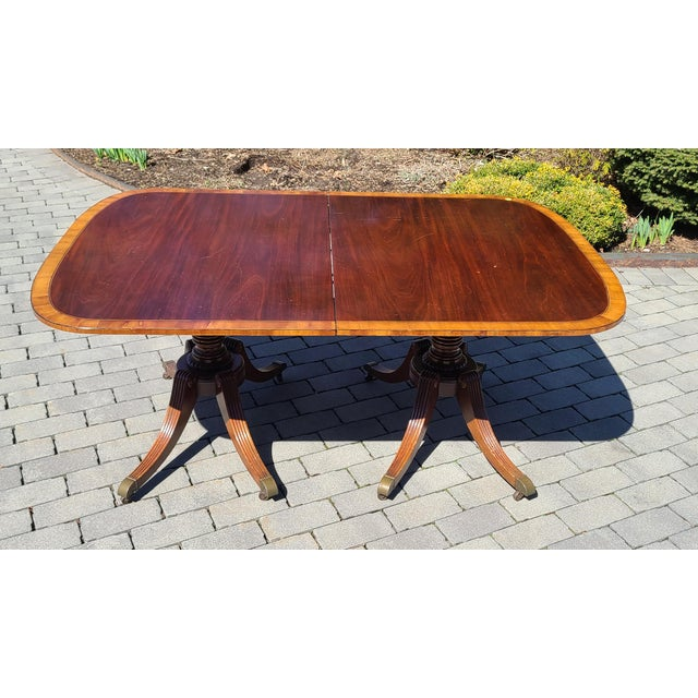 This is a really nice antique banded mahogany Georgian style dining room table made by Baker Furniture, late 1930s....