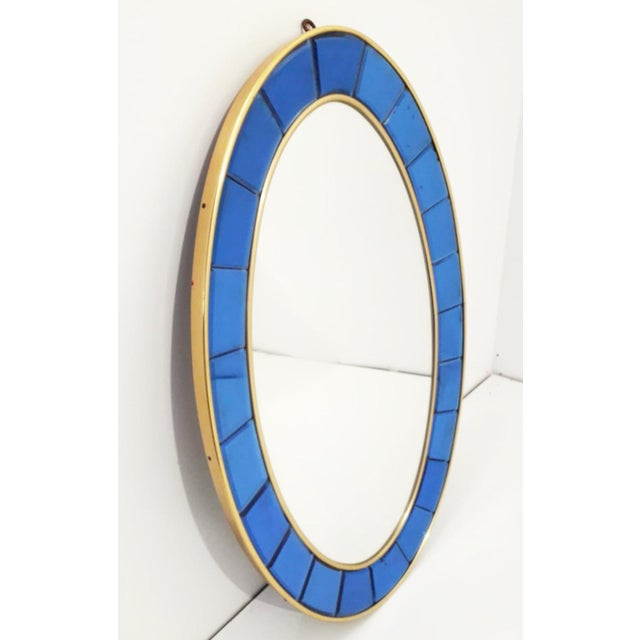 Italian vintage large oval wall mirror surrounded by beveled cobalt blue glass panels, placed on gilt brass and wooden...