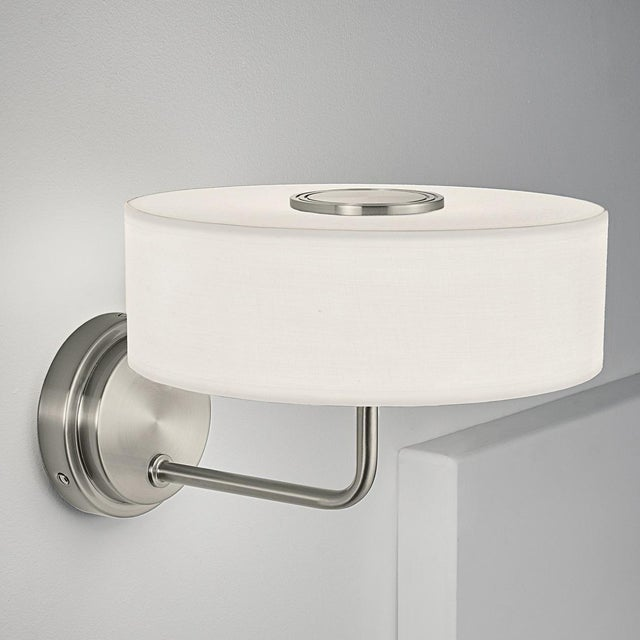 Brushed nickel wall light with an off white fabric shade secured with a decorative grooved disc. There is an integral LED...