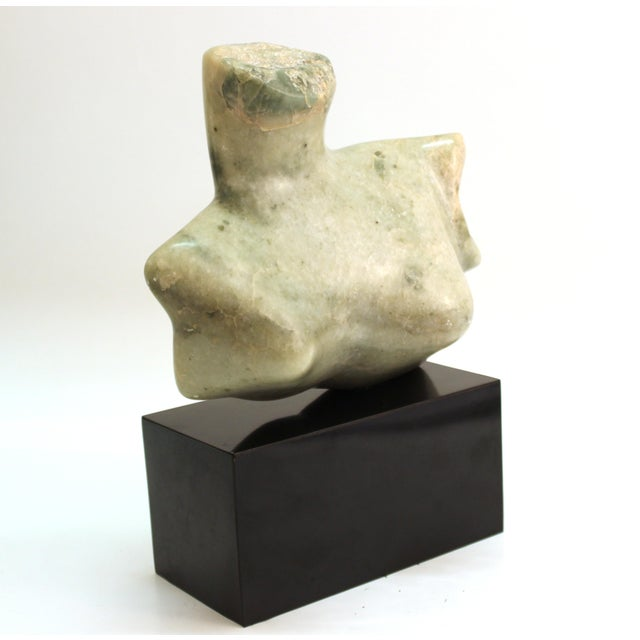 Mid-Century Modern abstract sculpture depicting a female chest or bust, carved in stone. The piece sits atop a black base...