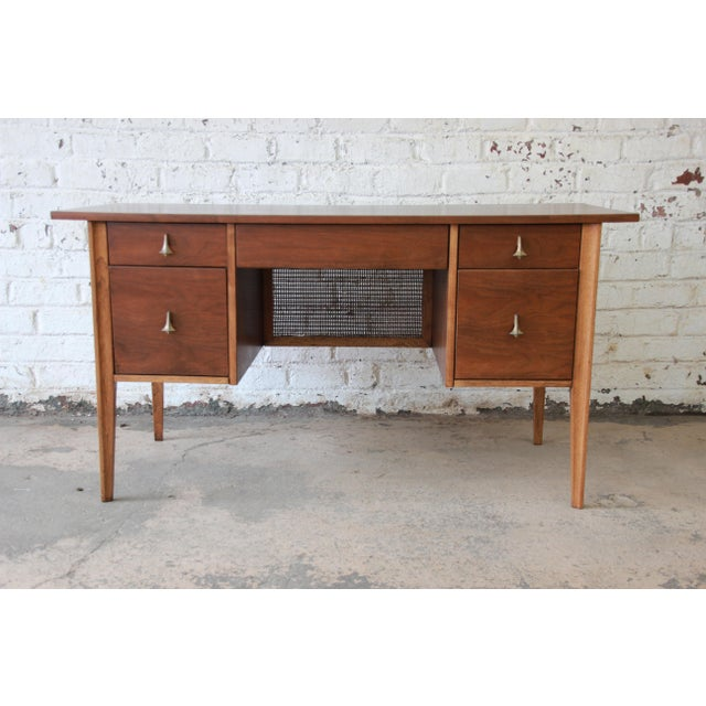 Offering a rare and exceptional Broyhill Brasilia mid-century modern sculpted walnut desk. The desk features gorgeous two-...