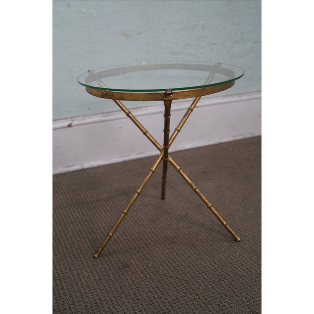 Small, vintage side table featuring a tripod base finished in a gilt metal, faux bamboo style. A circular glass top...