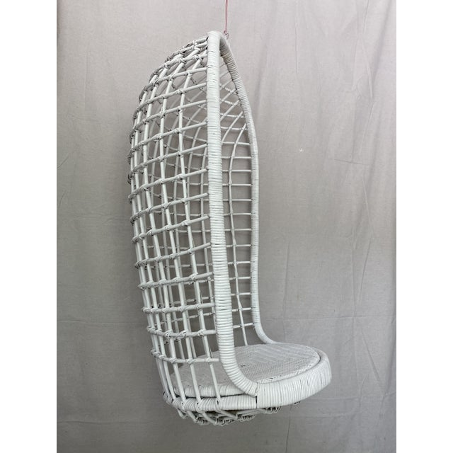 Vintage hanging rattan egg chair. Oblong egg shape with woven rattan frame and woven caning seat. Has a metal ring to hang...