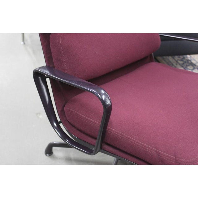 Pair of Herman Miller Eames Aluminum Group executive chairs. Burgundy upholstery. Three cushion seat back. Deep violet...