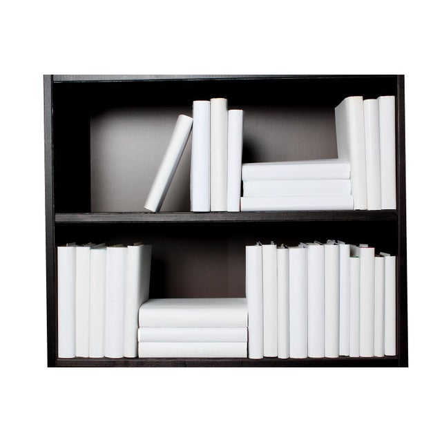 The Modern White Wrapped Book Wall features fifty hardcover books, each housed in custom wrapped crisp white dustjackets...