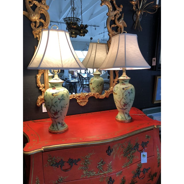 A beautiful pair of celadon green painted table lamps having birds and foliage, bronze gold details and very pretty...