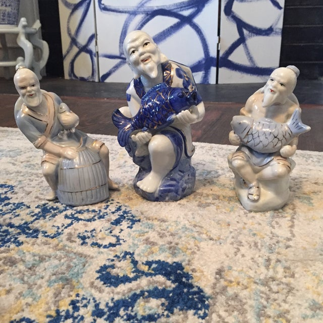 Set of 3 decorative blue and white Chinese men. All three are holding a fish Hand painted blanc de chine figurines. Two...