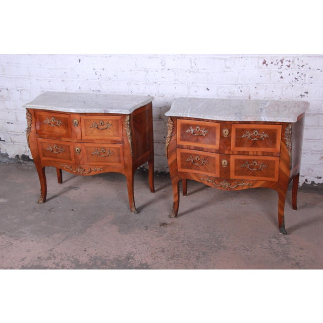 Offering an exceptional pair of Louis XV style marble top nightstands or commodes. The chests feature stunning inlaid...