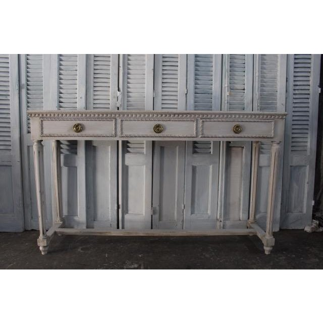 Vintage French Louis XVI console table made of solid oak with three fitted drawers. Newly refinished with a distressed...