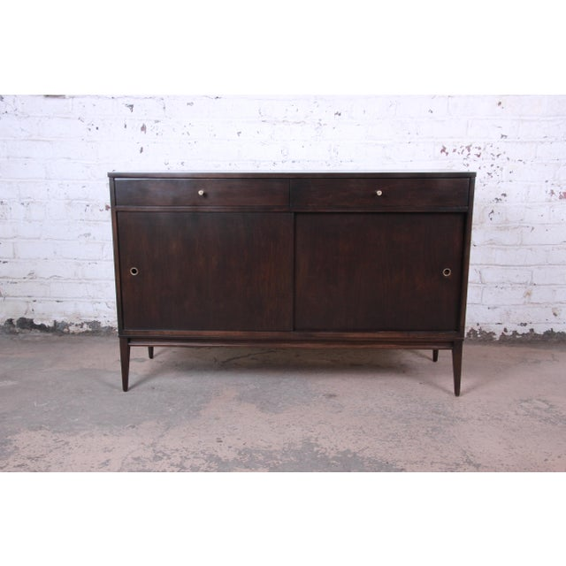 Offering an exceptional mid-century modern sideboard credenza designed by Paul McCobb for his Planner Group line for...