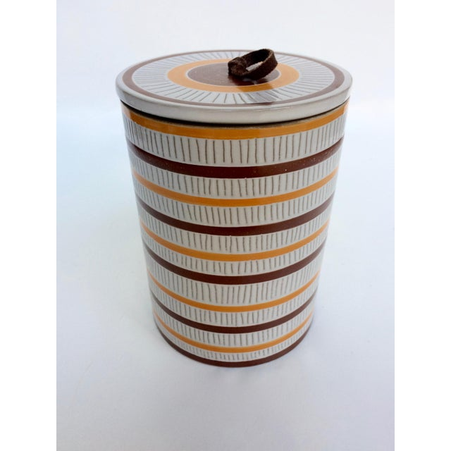 Early Jonathan Adler sgraffito canister in large. Off white base with brown and yellow detailing, with a brown leather...