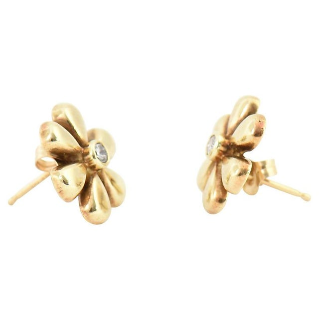 14K yellow gold daisy earrings set with a .07 carat diamond in the center of each. Post backs. Marked: 14K. COLOR: gold...