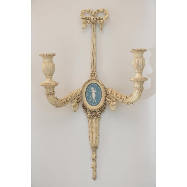 Opposing pair of sconces, of wood, having distressed painted finish, each surmounted by intricately carved bow; two...