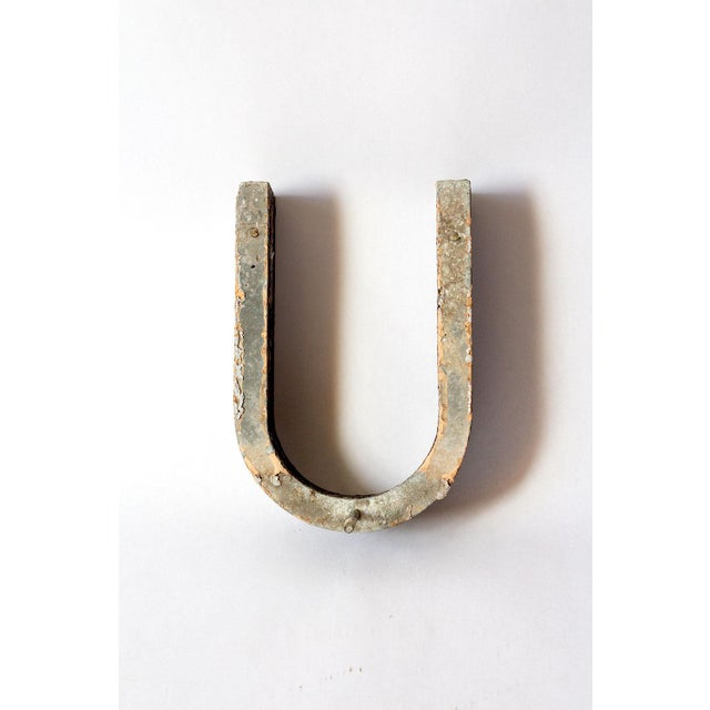 """Beautifully aged metal letter U. Black chippy paint shows a pop of muted pink underneath. Screw adds 1"""" D."""