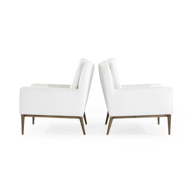 Set of iconic lounge chairs designed by Paul McCobb for Directional, circa 1950s. Newly upholstered in white linen,...