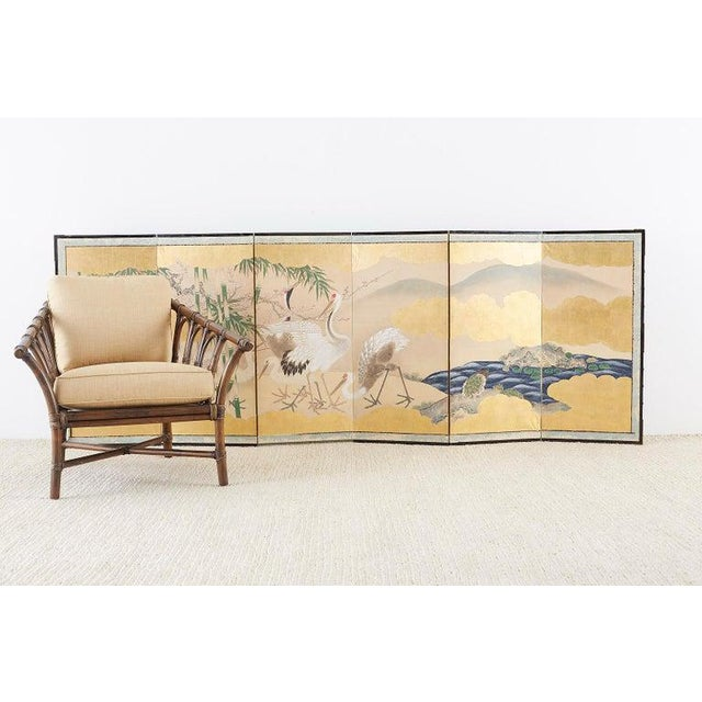 Fascinating pair of Japanese six-panel Meiji period screens depicting red-crowned cranes and minogame in landscape scenes....