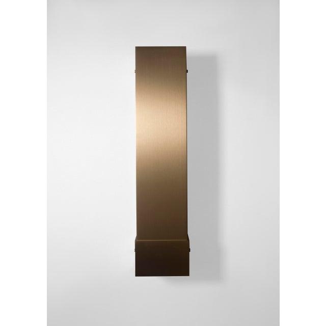 This contemporary light made of brushed brass is part of the Orphan Work brand and can be used as a wall sconce, picture...