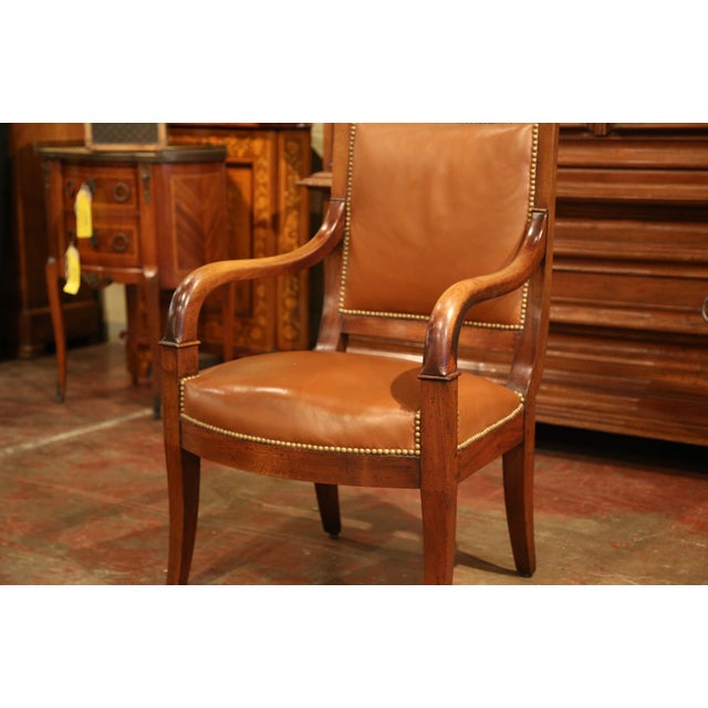 This elegant antique fruit wood armchair was created in Paris, France, circa 1850; the comfortable desk chair with...