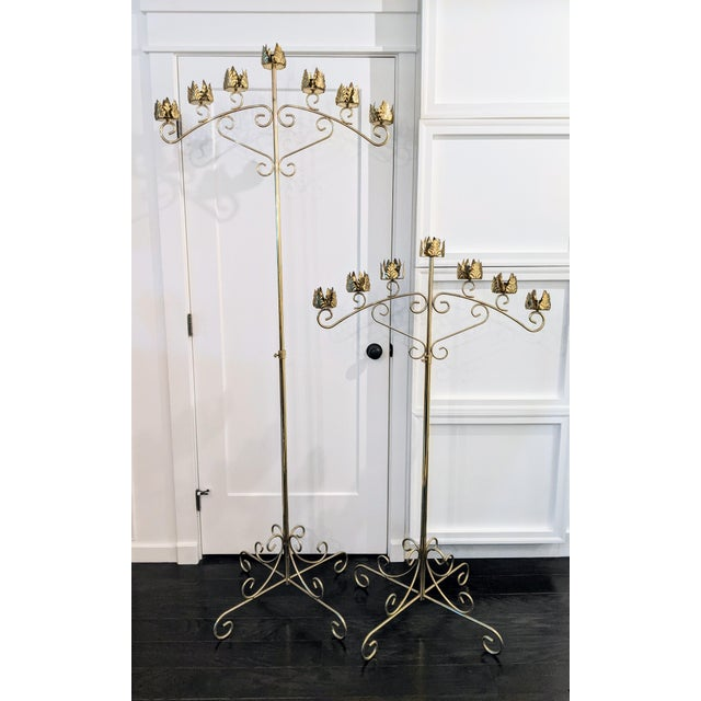 A striking pair of free-standing, vintage brass candelabras with seven candle holders each and an elaborately rendered...