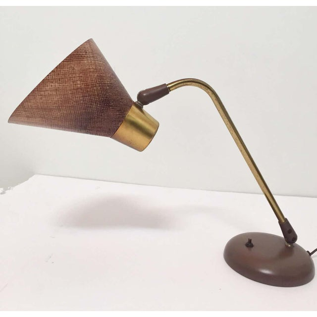 Nice and unique table or desk lamp designed by Gerald Thurston for Lightolier. The lamp has a fiberglass shade, a brass...