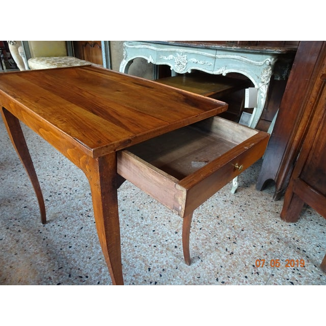 A charming French mid 19th Century cherry wood side table with molded top and one drawer on the right side of the table....