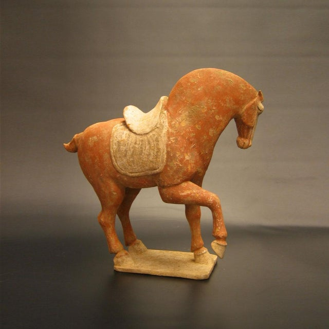 This gorgeous example still retains much of its original red polychromy and the white saddle is delicately incised. The...