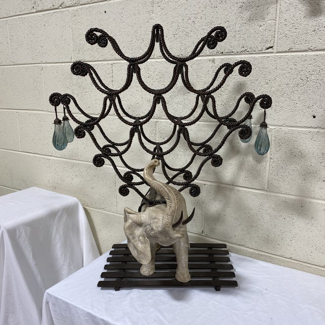 This is a signed Hilda Flack heavy (30lbs) scrolled and twisted iron wine rack with a stone carved elephant with iron...