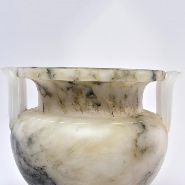 """Custom made for us in Italy, this hand-crafted alabaster vase is 10"""" high and has a pale beige body with dark gray..."""