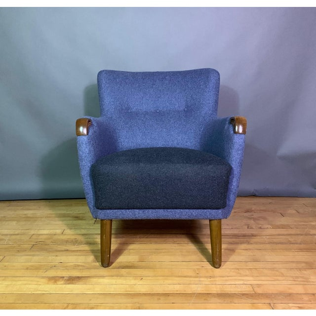 The perfectly shaped Danish easy chair from the 1950s with hand-carved teak arm end-points. Somewhat diminutive as is...