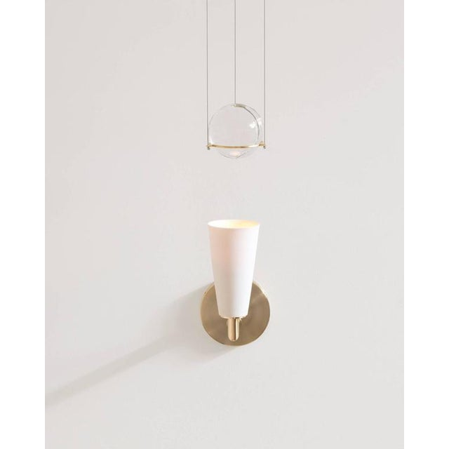 Grace is a contemporary union of softness and structure. A porcelain and brass-mounted light illuminates and engages an...