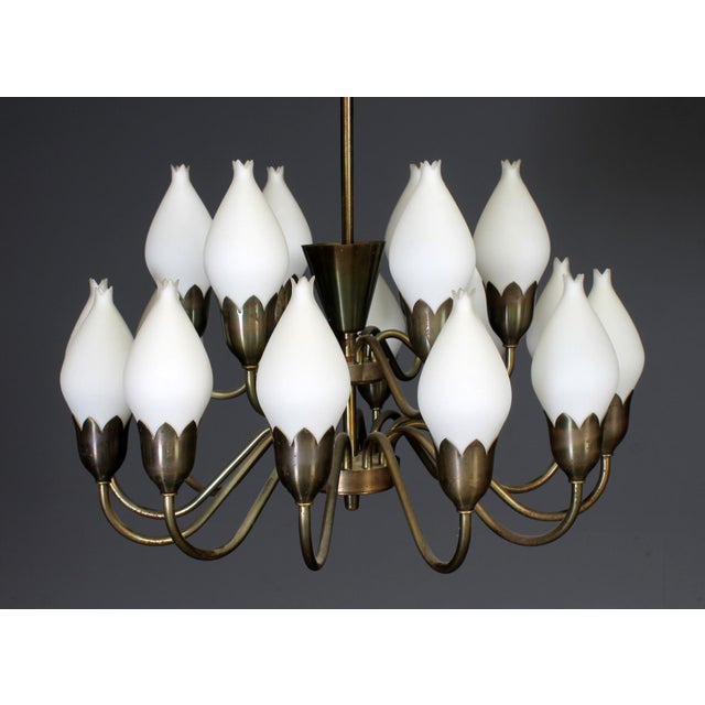 "This ""Tulip"" chandelier with patinated brass on two animals, with 18 bulb-shaped opal glass shades was made in Denmark by..."