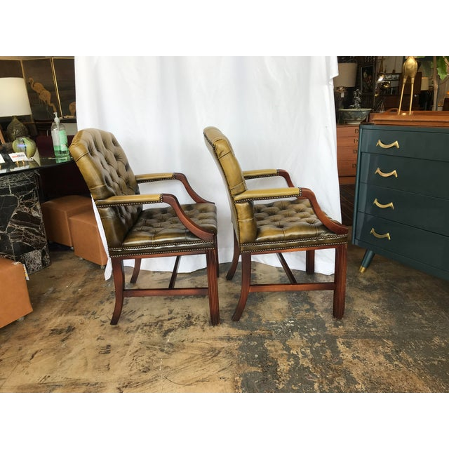 Pair of olive green tufted chesterfield guest chairs with wood legs and armrests. The chairs have brass braids.