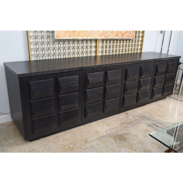 The rectangular top above four doors with pyramidal lozenges overall on the doors, the finish in cerused ebonized matte...