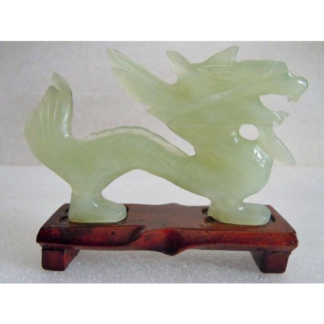 This dragon has very fine cut features. Mounted on a wooden stand, the stone is a faintly translucent light green in...