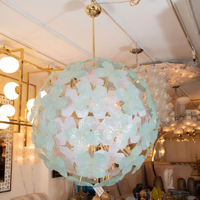 Spherical pale green flower form chandelier with brass details.