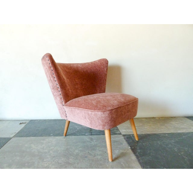 1950s Danish Cocktail Chair newly upholstered in Pink velvet fabric with nailhead detailing on the back and natural wood...