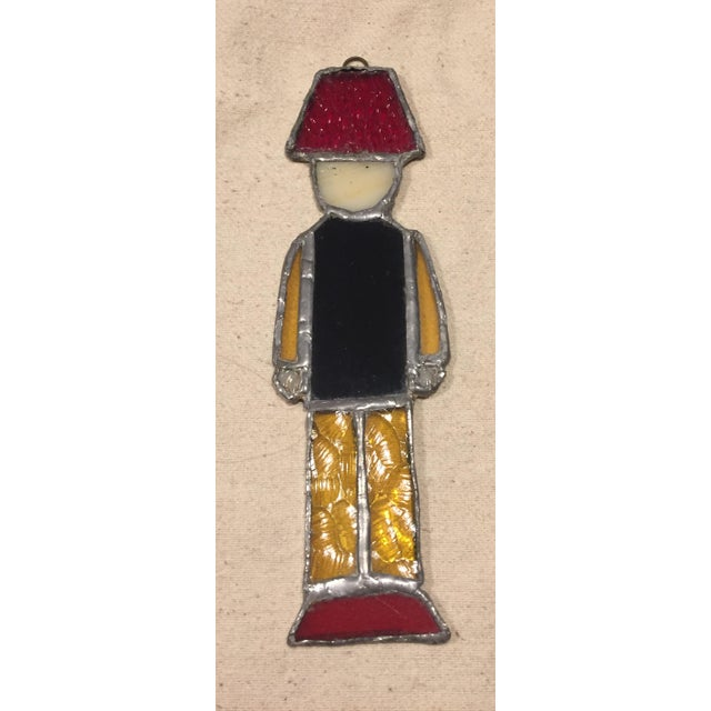This is an adorable stained glass nutcracker or toy soldier. It can be hung on a window to catch the light or on a...