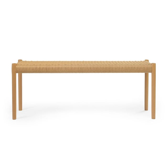 A modest bench comprising a wickered papercord woven seat on a beech frame with round legs, model no. 63B. With label to...