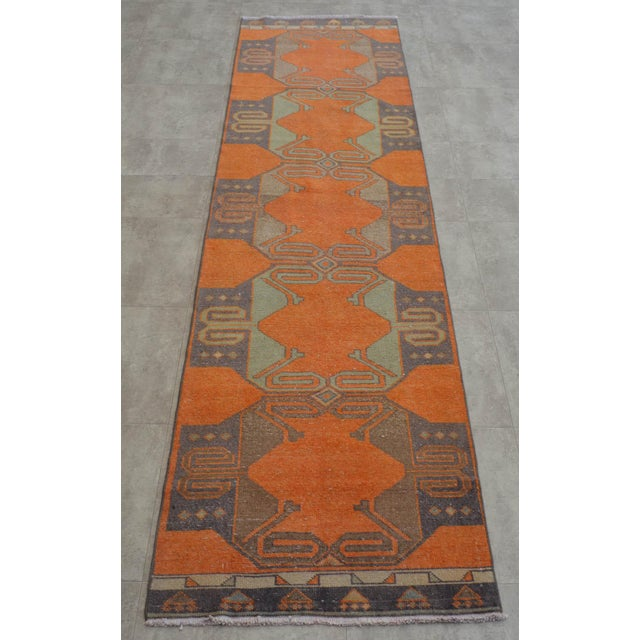 Vintage 1960s distressed Turkish Oushak rug runner. with orange field and shades of green, dark gray and blue throughout....