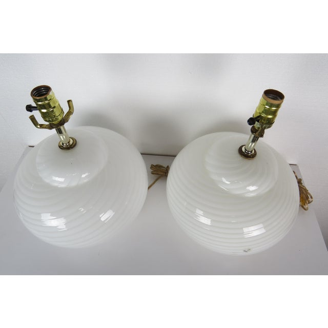 A pair of mid-century modern white swirl Vetri Murano glass lamps with three light settings. 3rd Generation in the Arts,...