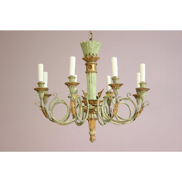 Beautiful, 1960s Italian painted and parcel-gilt carved wood and iron chandelier in the neoclassical style. This elegant...