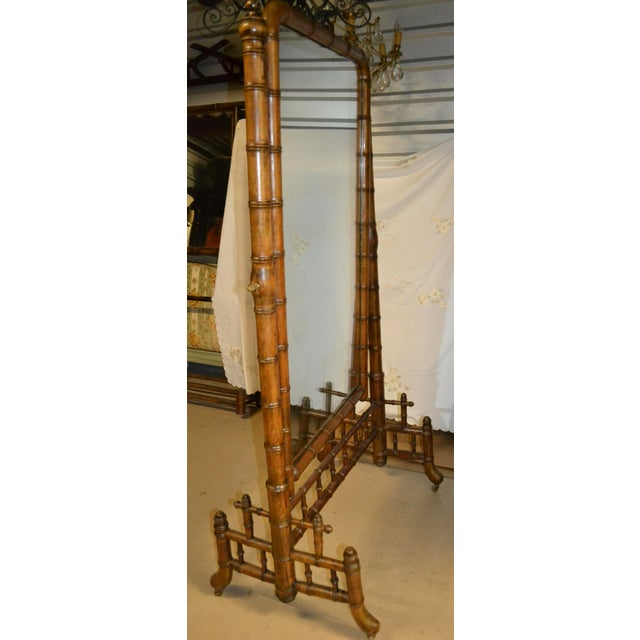 A faux bamboo freestanding cheval mirror featuring a full length mirrored glass panel framed in turned wood with a bamboo...
