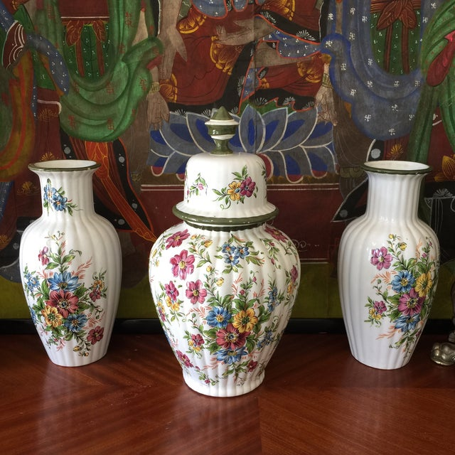 "Collection of floral Dutch vases with green trim. Small vases are 12"" x 5.5"". Top to large vase is 6"" x 5.25"". Four pieces..."